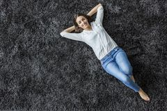 Woman laying on the carpet. Young woman laying on the carpet stock image
