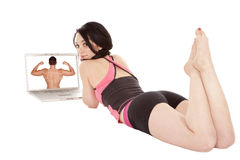 Woman laying by computer looking back Royalty Free Stock Photography