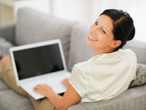 Woman laying on couch and working on laptop Stock Image