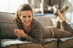 Woman laying on divan in loft apartmen. Portrait of smiling young woman laying on divan in loft apartment stock image
