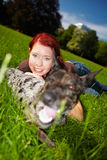 Woman laying with dog in park Stock Photography