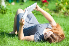 Woman laying down with book in hands Royalty Free Stock Image
