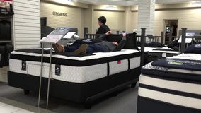 Woman laying down on display bed. Inside The Bay store stock video