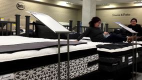 Woman laying down on display bed. Inside The Bay store stock video footage