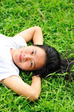 Woman laying down in grass Stock Photos