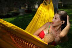 Woman laying down on a hammock. Attractive young woman laying down and relaxing on a white hammock while on vacation in a tropical garden Stock Image