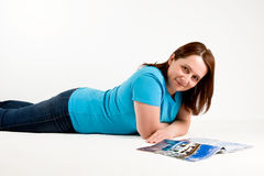 Woman laying down and reading magazine Royalty Free Stock Image