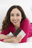 Woman laying and eating chocolate Stock Photos