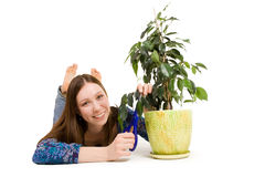 Woman laying on the floor cutting plant Royalty Free Stock Photo