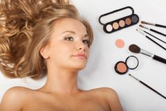 Woman laying on floor with eyeshadows and brushes Stock Photography