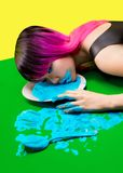 Woman laying on floor with face on plate. With blue liquid Stock Image