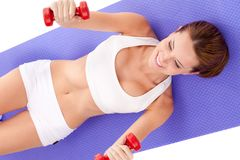 Woman laying on the floor and lifting dumbbells Royalty Free Stock Images