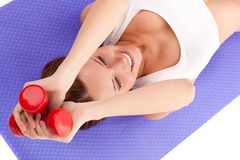 Woman laying on the floor and lifting dumbbells Royalty Free Stock Image