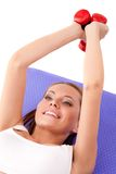 Woman laying on the floor and lifting dumbbells Royalty Free Stock Photography
