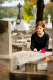 Woman Laying Flower on Grave stock photos