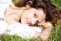 Woman laying in the grass. Happy woman smiling laying in the grass in the summer Royalty Free Stock Photos