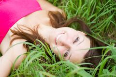 Woman laying in grass Stock Images