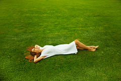 Woman laying on a grass Stock Photography