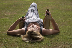 Woman laying on grass clutching beer bottles Royalty Free Stock Photography