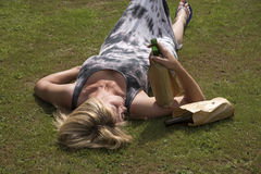 Woman laying on grass clutching beer bottles Royalty Free Stock Image