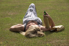 Woman laying on grass clutching beer bottles Royalty Free Stock Images