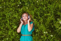 Woman laying on grass with headphones Stock Photography