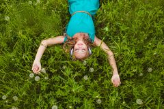 Woman laying on grass with headphones Royalty Free Stock Photography
