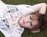 Woman laying in grass Stock Photos