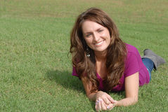Woman laying in grass smiling. Young female model laying in the grass smiling and happy Royalty Free Stock Photo