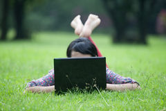 Woman laying on grass using laptop Stock Image