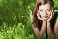 Woman laying in a green field Stock Images
