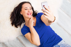 Woman laying on the ground and taking selfie Royalty Free Stock Photos