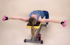 Woman laying on a gym training bench exercising Royalty Free Stock Photography