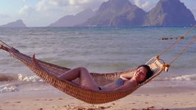 Woman Laying In Hammock On The Tropical Beach. Woman Laying In Hammock On Beautiful Tropical Beach At Sunset stock video footage