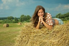 Woman laying on hay bail Stock Images