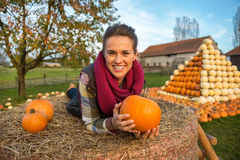 Woman laying on haystack with pumpkins Royalty Free Stock Photo
