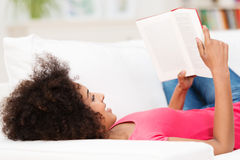 Woman laying on her back on the sofa, reading Royalty Free Stock Photo