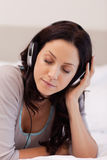 Woman laying on her bed enjoying music Royalty Free Stock Photo
