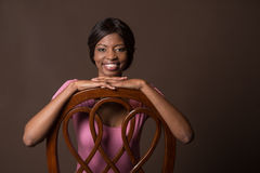 Woman laying her hands on chair and smiling. African American woman in chair on brown background Stock Photos
