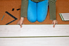 Woman laying laminate flooring. The photo shows a woman laying laminate flooring board stock photo