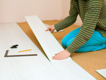 Woman laying laminate flooring. The photo shows a woman laying laminate flooring board stock images