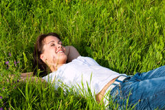 Woman laying on a lawn and is dreaming Royalty Free Stock Photography