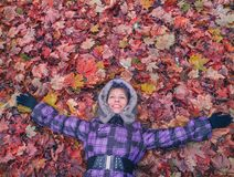 Woman laying in leaves happy. Royalty Free Stock Photo
