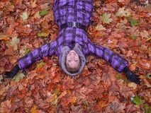 Woman laying in leaves happy. Royalty Free Stock Images