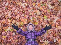 Woman laying in leaves happy. Stock Photo