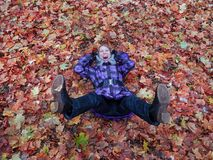 Woman laying in leaves happy. Royalty Free Stock Image
