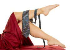 Woman laying legs out of sheet with mans tie Stock Images