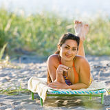 Woman laying on lounge chair at beach Stock Photos
