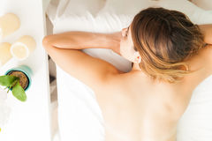 Woman laying on a massage bed. Pretty young brunette laying on a spa bed waiting for her massage, as seen from above Royalty Free Stock Photography