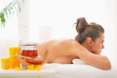 Woman laying on massage table with honey spa therapy ingredients Stock Photography